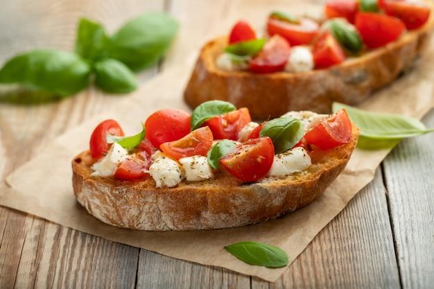 Bruschetta com tomate, queijo mussarela e manjericão. Foto Premium