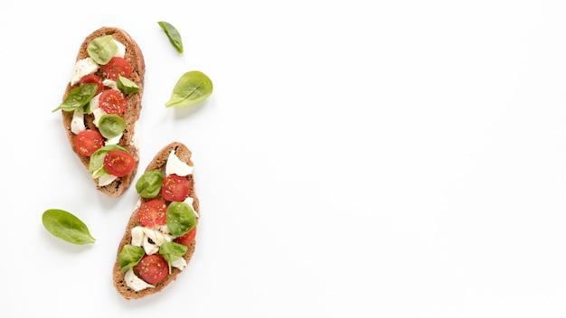 Bruschetta deliciosa com folhas de manjericão isolado na superfície branca Foto gratuita