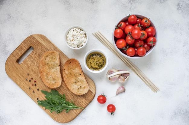 Bruschetta italiano com tomates roasted, mozzarella e ervas em uma placa de corte. Foto Premium