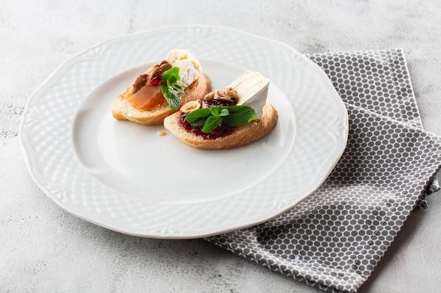 Bruschettas com legumes. comece pratos com tomate cereja, cream cheese. deliciosos petiscos com chouriço e tomates assados. composição de alimentos, saborosa refeição italiana. pão com queijo Foto Premium