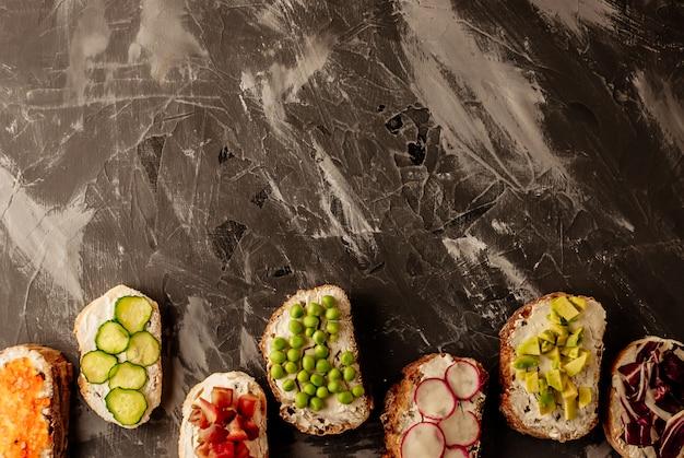 Brushetta ou tapas espanholas tradicionais. os petiscos italianos dos antipasti dos aperitivos ajustaram-se na placa de madeira. Foto Premium