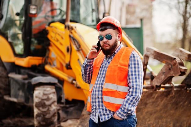 Brutal barba trabalhador homem terno trabalhador da construção civil no capacete de segurança laranja, óculos de sol contra traktor com celular na mão. Foto Premium