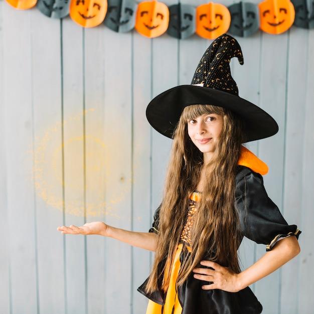 Bruxa jovem mostrando feitiçaria no halloween Foto gratuita