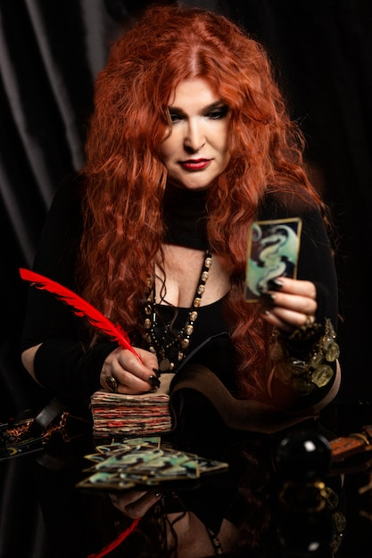 Bruxa mulher, cartomante com cabelo vermelho executa um ritual mágico. leitura de cartões. Foto Premium