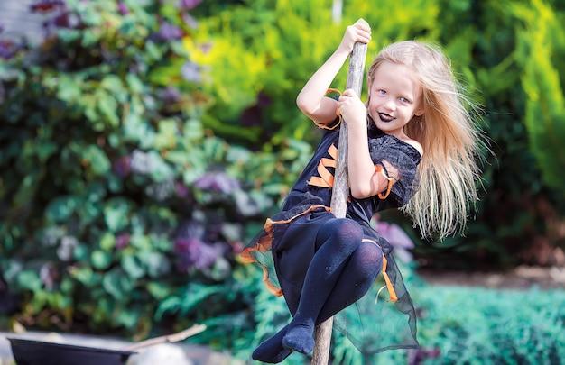 Bruxinha feliz divirta-se ao ar livre no halloween. doçura ou travessura. Foto Premium