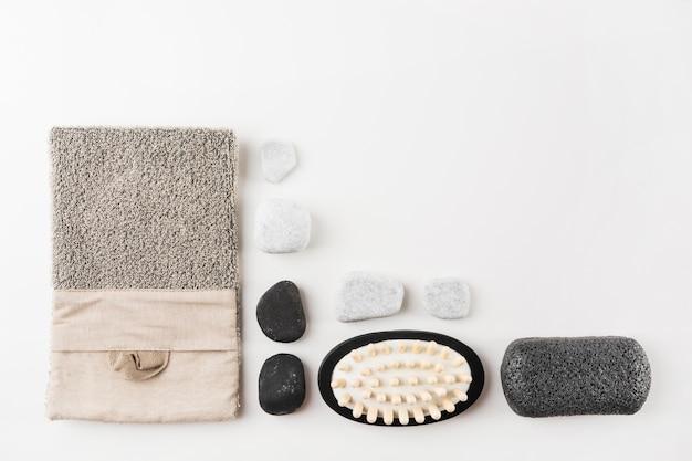 Bucha; pedras de spa; massagem escova e pedra-pomes isolada no fundo branco Foto gratuita