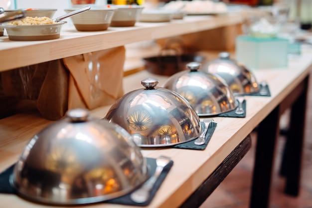 Bufete em um restaurante ou hotel. pratos de metal com tampas. Foto Premium