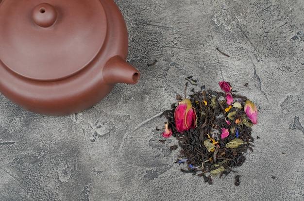 Bule com chá e uma pilha de folhas de chá soltas perfumadas e botões de flores secas Foto Premium