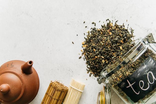 Bule de barro; roll-up placemat com derramado de chá de ervas secas derramado do frasco de vidro Foto gratuita