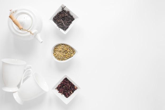 Bule de chá; copo cerâmico; flores secas de crisântemo chinês; folhas de chá secas no pano de fundo branco Foto gratuita