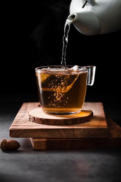 Bule de chá derramando chá close-up Foto gratuita