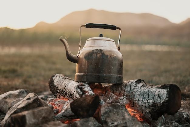 Bule de chá no fogo da montanha Foto gratuita