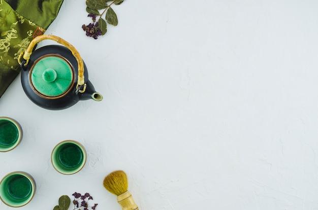 Bule de ervas com xícaras de cerâmicas e pincel isolado no fundo branco Foto gratuita