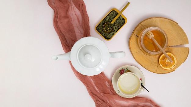Bule de ervas; sai; dipper de mel; citrinos secos; xícara de cerâmica e pires em fundo branco Foto gratuita