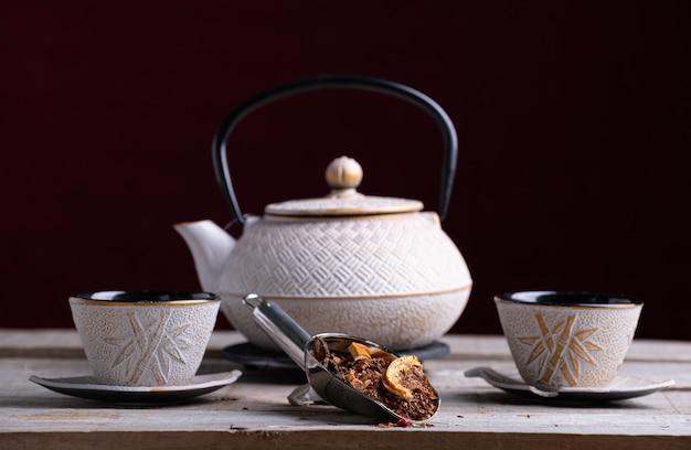 Bule de porcelana branca e dois copos para servir o chá com palin picante Foto Premium