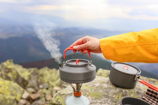 Bule de viagem de acampamento e xícaras de chá de acampamento nas montanhas dos cárpatos Foto Premium