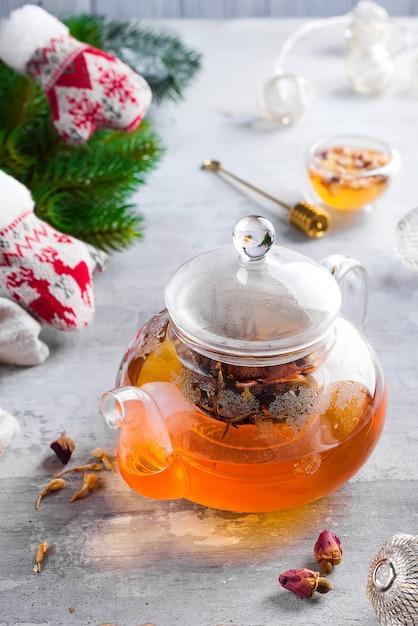 Bule de vidro com chá de flores amarradas, chá quente em bule de vidro e mel com vara de metal mel Foto Premium