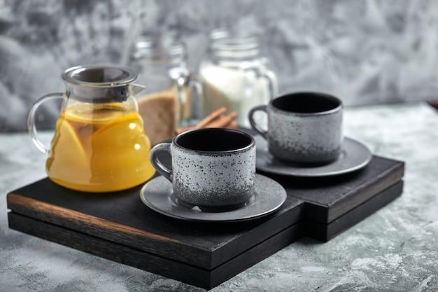 Bule de vidro transparente com chitrus chá e xícaras, jogo de chá em uma mesa de madeira. close-up, cinza, luz suave. Foto Premium