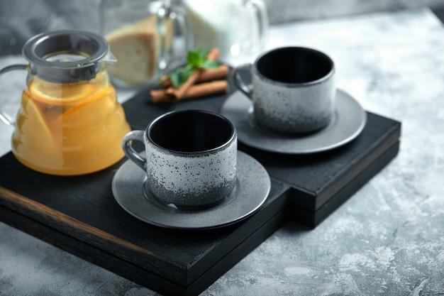 Bule de vidro transparente com chitrus chá e xícaras, jogo de chá em uma mesa de madeira Foto Premium