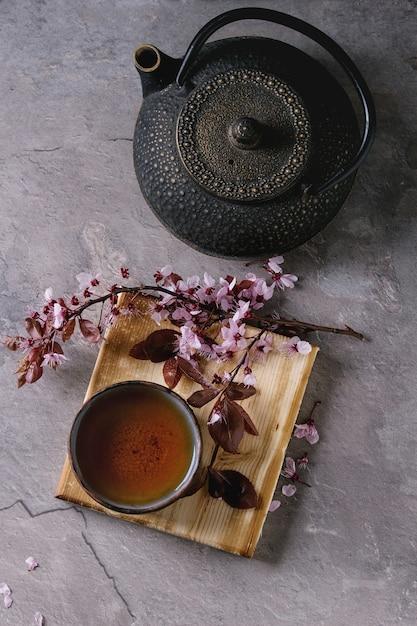 Bule e xícara de chá com ramo de flor Foto Premium