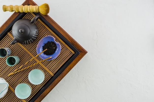 Bule japonês tradicional; escova; ervas e xícaras na bandeja de madeira no fundo branco Foto gratuita