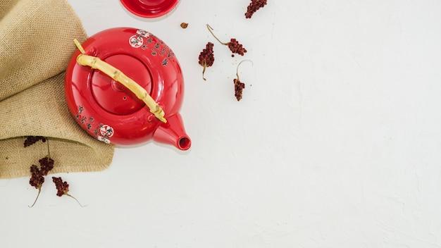 Bule tradicional oriental vermelho com ervas isolado no fundo branco Foto gratuita