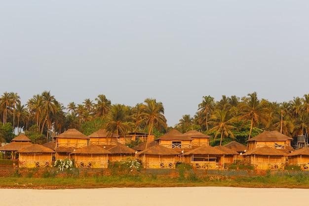 Bungalow na costa do mar, uma rede de casas de junco de bambu e folhas de palmeira. praia aconchegante, goa, na índia. Foto Premium