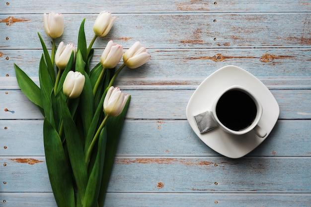 Buquê branco de tulipas em um fundo azul de madeira com uma xícara de café Foto Premium