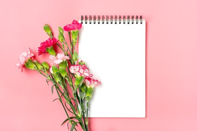Buquê colorido de diferentes flores de cravo rosa, caderno branco sobre fundo rosa Foto Premium