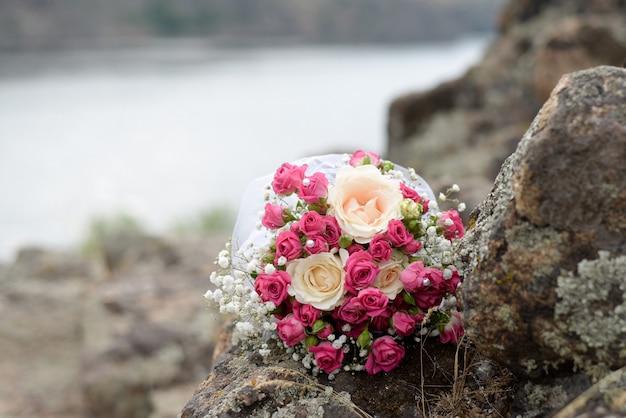Buquê da noiva de rosas cor de rosa e branco flores encontra-se em um log pelo lago Foto Premium