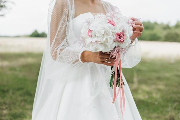Buquê de casamento bonito feito de narcisos brancos com meio rosa nas mãos da noiva ao ar livre Foto gratuita