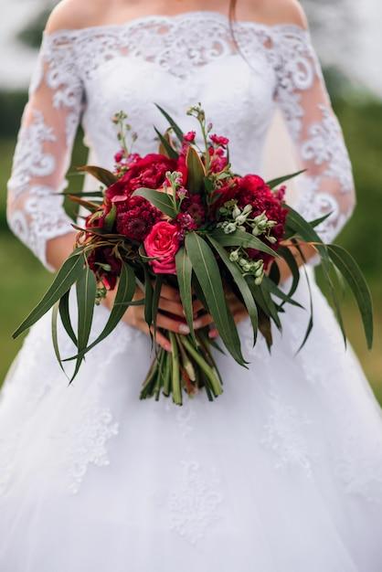 Buquê de casamento com peônias vermelhas nas mãos da noiva em um vestido branco Foto Premium