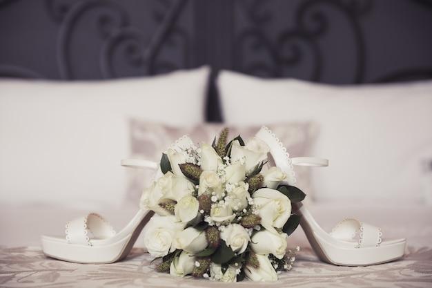 Buquê de casamento e sapatos no quarto Foto Premium