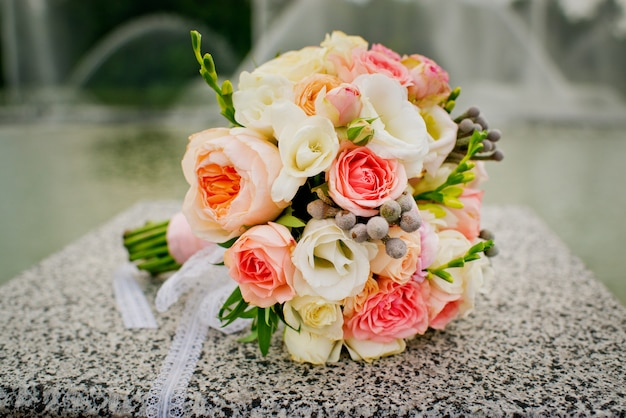 Buquê de casamento elegante e bonito no fundo das fontes Foto Premium