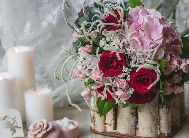 Buquê de casamento em um pedaço de madeira com velas brancas Foto gratuita