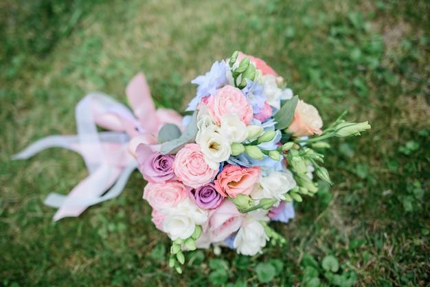 Buquê de casamento feito de rosas e botões verdes situa-se no gramado Foto Premium