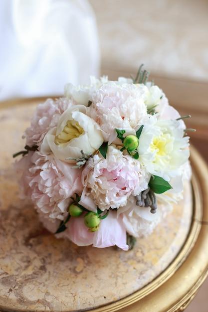 Buquê de casamento lindo na mão da noiva de peônias brancas Foto Premium