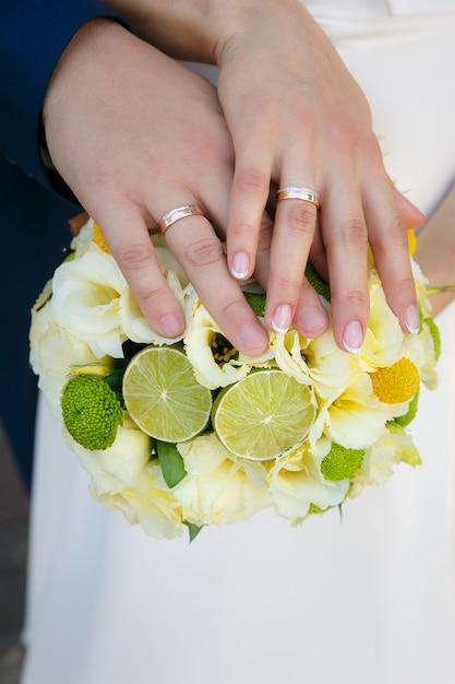Buquê de casamento nas mãos da noiva e do noivo Foto Premium