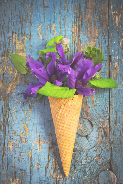 Buquê de clematis azul no cone de waffle de sorvete Foto Premium