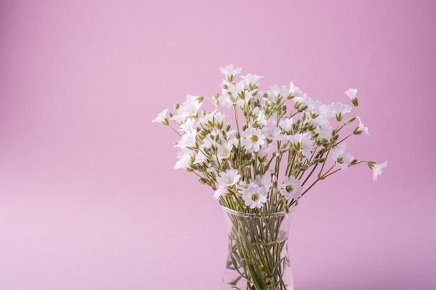 Buquê de flores brancas em vaso de vidro rosa Foto Premium