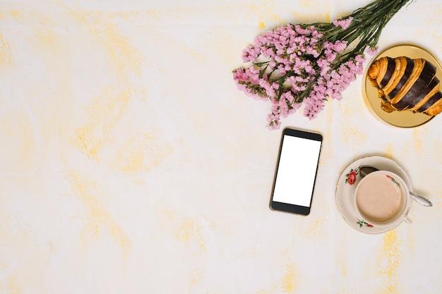 Buquê de flores com smartphone, café e croissant na mesa Foto gratuita