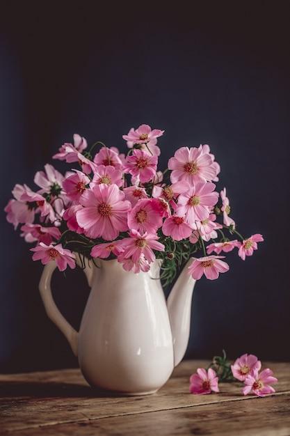Buquê de flores cor de rosa. cosmea. fundo azul, pratos brancos Foto Premium