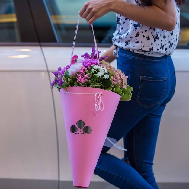 Buquê de flores de cardos e fio dental holded por uma menina em jeans Foto gratuita