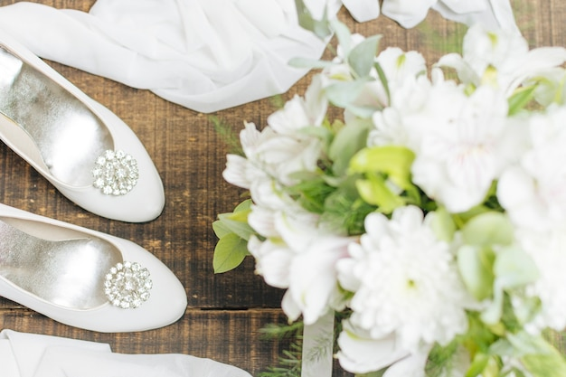 Buquê de flores de casamento; saltos altos e lenço na cadeira de madeira Foto gratuita