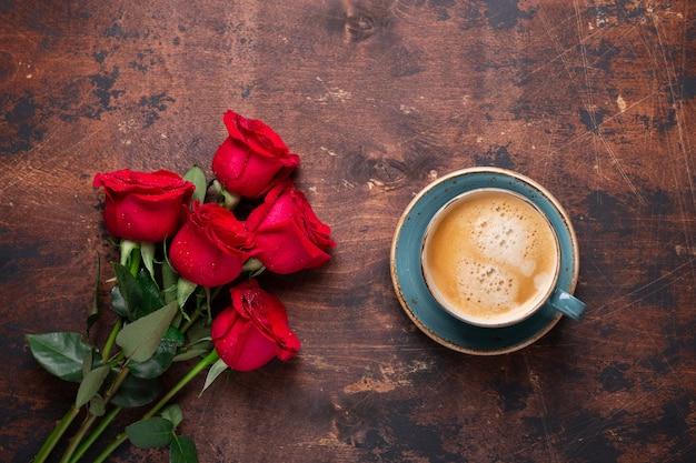 Buquê de flores de rosas vermelhas e xícara de café sobre fundo de madeira Foto Premium