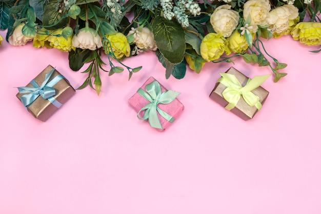 Buquê de flores e caixas de presente em fundo rosa, vista superior Foto Premium
