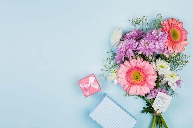 Buquê de flores frescas com título na tag perto de caixa de presente e notebook Foto gratuita