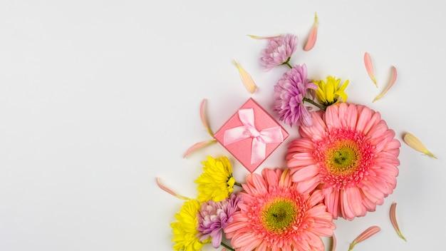 Buquê de flores frescas perto de caixa de presente e pétalas Foto gratuita