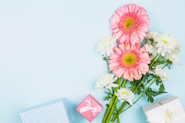 Buquê de flores frescas perto de caixas de presentes Foto gratuita