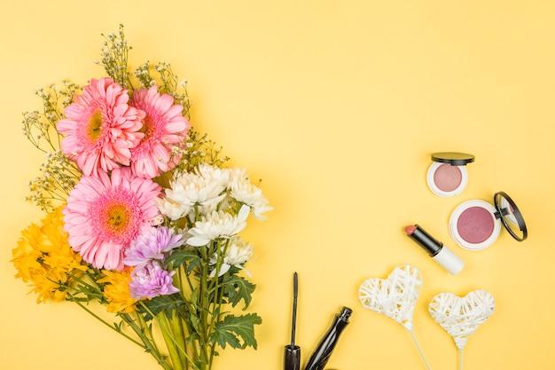 Buquê de flores frescas perto de corações ornamentais em varinhas e batons com pós Foto gratuita